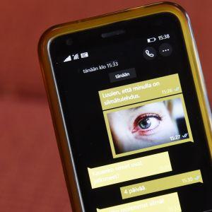 Chat-keskustelu ja valokuva silmästä puhelimen näytöllä.
