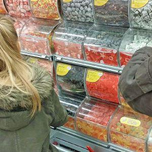 Kuvassa kaksi ihmistä ottaa irtokarkkihyllystä irtokarkkeja