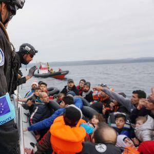 Rajavartioita ja veneellinen pakolaisia.