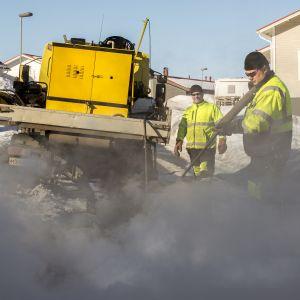Työmiehet sulattavat jäätynyttä viemäriä höyrynkehittimellä.