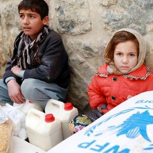 Lapset istuvat ruokasäkkien vieressä Kabulissa.