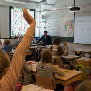 Oppilaat viittaavat matematiikan tunnilla.
