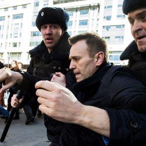 Kaksi poliisimiestä karvalakeissa kuljettaa Navalnyia kainaloista nostaen. Taustalla näkyy ihmisjoukkoa ja auringon kirkkaasti valaisema kerrostalon seinä. Navalnyi on paljan päin, mustassa takissa.