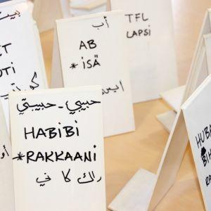 Arabian kielisiä sanakylttejä pöydällä.