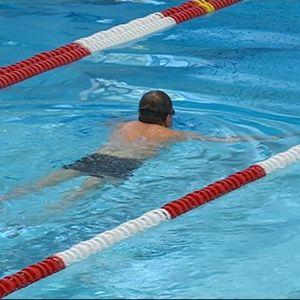 Mies ui uimahallissa.
