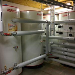 Maalämpöjärjestelmään kuuluvia säiliöitä ja putkia lämmönjakohuoneessa.