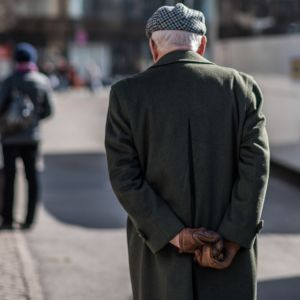 Eläkeläinen kävelee kadulla.