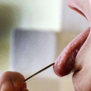 Naisella on suu auki ja lusikka suussa.