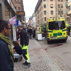 Ambulansseja kadulla, jonka molemmin puolin on kauppoja. Kadulla on paljon ihmisiä.