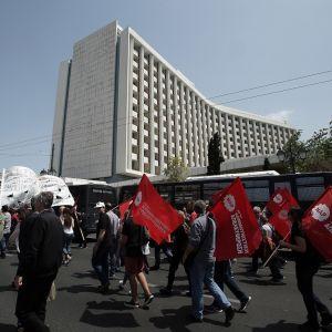 Joukko punalippuja kantavia mielenosoittajiia kulkee vaalean kerrostalon editse.