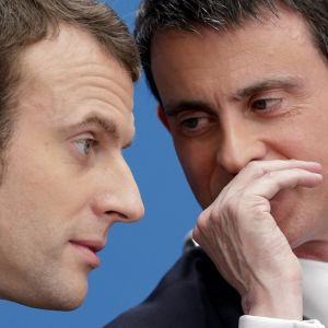 Valls kuiskaa kätensä suojasta jotain Macronille