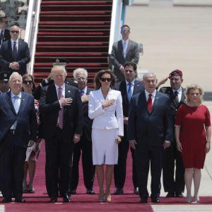 Kuusikko seisoo lentokoneen portaiden edessä. Taustalla muita ihmisiä.