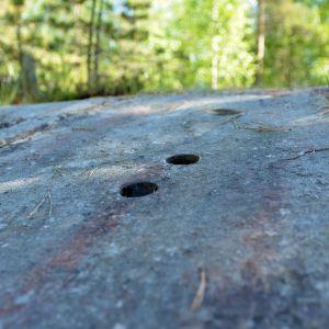 Kalliossa näkyy kaksi kairausreikää.