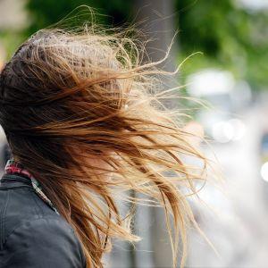 Pitkät hiukset liehuvat kovassa tuulessa.