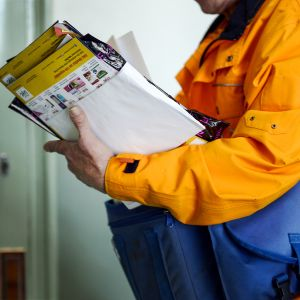 postinkantaja pitelee postinippua