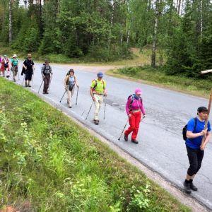 Ihmisiä kävelee tienviertä.
