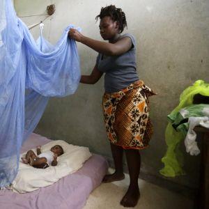 Zamble Lou Irie Sabine asentaa hyttysverkon kolmen kuukauden ikäiselle lapselleen Yao Melvinille Abidjanissa Norsunluurannikolla huhtikuussa 2017.