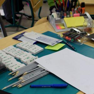 opettajan koulupöydällä odottavat uudet kumit ja kynät