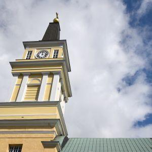 Oulun tuomiokirkon kellotapuli taustallaan sinisellä taivaalla valkoinen pilvi.