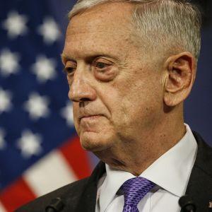 Jim Mattis tummassa puvussa, violetissa kravatissa, taustalla Yhdysvaltain lippu.