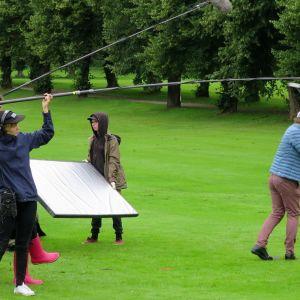 Kuvaustiimi nauhoittaa kun näyttelijät heiluttelevat mailoja golfkentällä