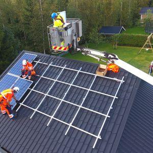 Miehiä asentamassa aurinkopaneeleja katolle.