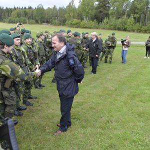 Ruotsin pääministeri Stefan Löfven kättelee sotilasta. Hänen takanaan kaempana kättelemässä on puolustusministeri Peter Hulqvist.
