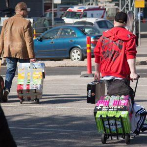 matkustajat kantavat olutlastia satamassa