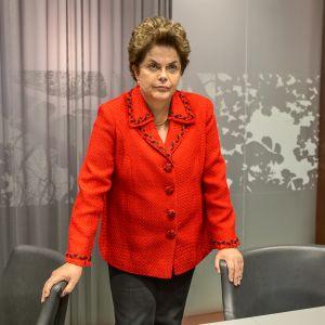 Dilma Rousseff nojaa seisoessaan kahteen tuoliin.