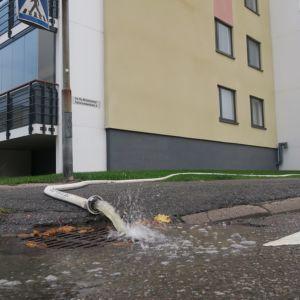 Kerrostalon kellarista pumpataan vettä, joka valuu letkusta sadevesiviemäriin