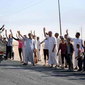 Kirkukin asukkaat ottavat vastaan shiiamilitioiden jäseniä, jotka saapuvat avolava-autolla.
