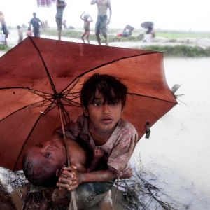 Rohingya-lapsia värjöttelee sateenvarjona alla Bangladeshissa.
