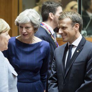 Merkel selin kameraan, May ja Macron kuuntelevat, mitä hän puhuu.