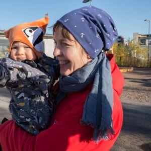 Runsaan vuoden ikäinen Alvar Merikanto äitinsä Maija Merikannon sylissä leikkipuisto Arabiassa.