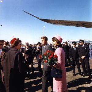 John F. Kennedy ja Jacqueline Kennedy lentokentällä. Heidän ympärillään on ihmisiä.