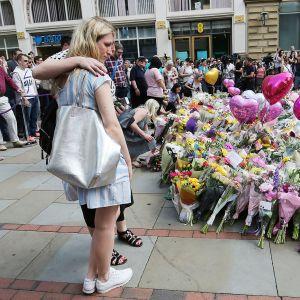 Ihmiset toivat kukkia terrori-iskussa kuolleiden muistolle Manchesterissa 25. toukokuuta.