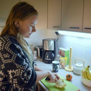 Nainen leikkaa kukkakaalia keittiössä.