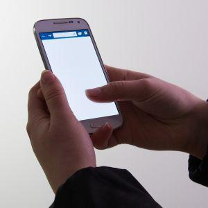 Nuori näppäilee älypuhelinta.