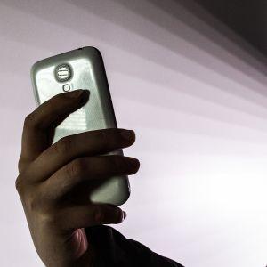 Nuori älypuhelin kädessään.