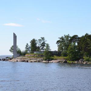 Varissaaren rantaa, jossa ravintolarakennus ja muistomerkki.
