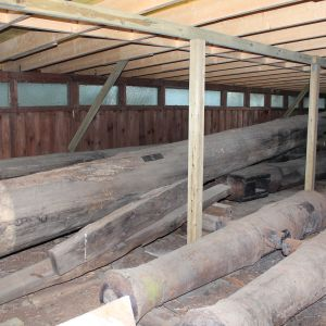 Hylyn rakenneosia ja tykkejä varastoituna huonokuntoiseen varastoon Kotkan Varissaaressa.