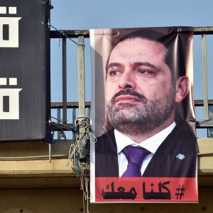 Hariria esittävä juliste roikkuu sillan kaiteesta. Vieressä on kirjoitusta mustalla pohjalla.
