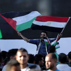 Mies heiluttaa palestiinalaisten ja Egyptin lippua väkijoukon yläpuolella.