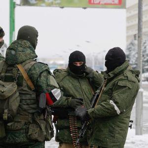 Neljä maastopukuista miestä kasvot peitettyinä ja aseet käsissään seisoo talvisella kadulla.