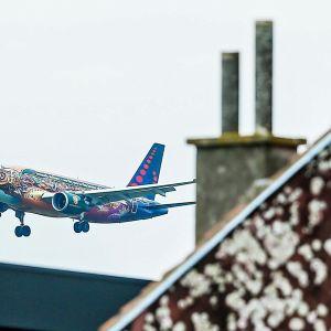 Brussels Airlinesin kone lähestyy Brysselin lentoasemaa, etualalla rakennuksen kattoa ja savupiippu.