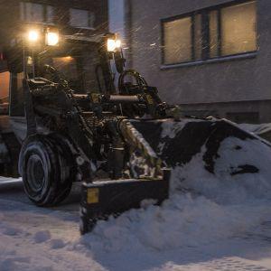Traktori auraa lunta lumipyryssä.