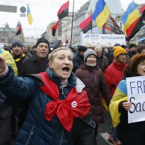 """Joukko mielenosoittajia kulkee Kiovan kadulla. Joukko kantaa Ukrainan lippuja ja Ukrainan toisen maailmansodan aikaisten nationalistitaistelijoiden punamustia lippuja. Etualalla nainen huutaa ja pui nyrkkiä. Kuvan oikeassa reunassa kävelee nainen, jonka kyltissä lukee """"Freedom Saakashvili""""."""