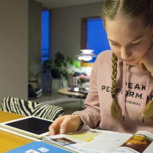 Tyttö lukee läksyjä pöydän ääressä.