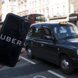 Etualalla näkyy älykännykkä, jonka näytöllä lukee isoilla kirjaimilla UBER. Taustalla näkyy musta Lontoon taksi.
