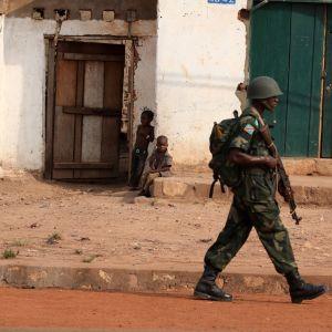 Sotilas kulkee aseen kanssa, talon edustalla istuu kaksi lasta.